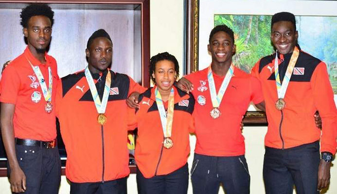 MEDAL STARS: Trinidad and Tobago's four individual medal winners and the captain of the gold medal-winning Girls beach soccer team pose with their Commonwealth Youth Games hardware at the VIP Lounge at Piarco International Airpot Tuesday night upon the team's return home from the Nassau, Bahamas event. From right are Tariq Horsford (silver) Jeron Thompson (bronze), Nia Honore (gold), Adell Colthrust (gold) and Jabari Grey (silver). —Photo: STEPHEN DOOBAY