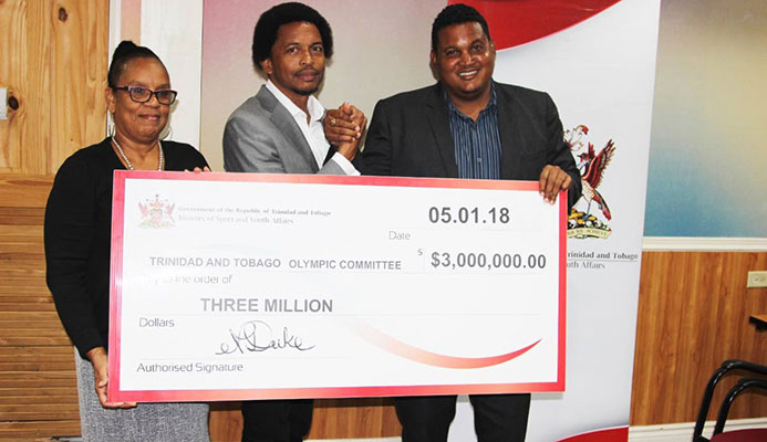 TEAM FUNDS: TTOC general secretary Annette Knott, left, and TTOC president Brian Lewis, centre, are presented with the ceremonial cheque by Minister of Sport and Youth Affairs Darryl Smith at Olympic House, Port of Spain recently.