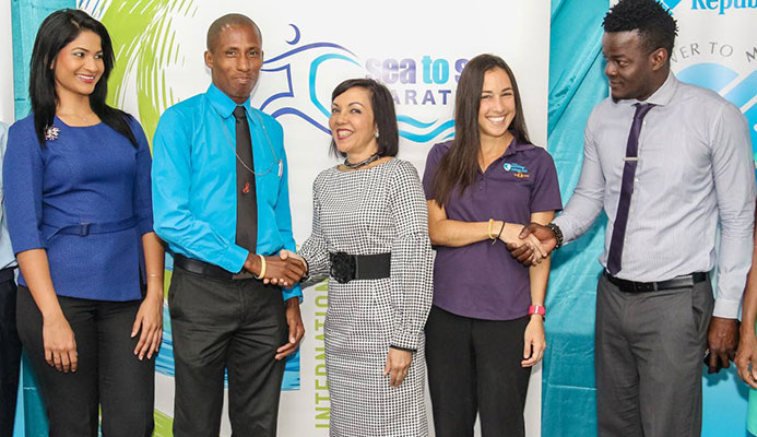 Veteran local long-distance runner Curtis Cox (second from left) greets Tisha Lee, manager of RBL, while marathon runner Sjaelan Evans (second from right) shakes hands with Kevon McKenna, activities coordinator of Sea to Sea Events Limited, at yesterday's launch. Also in photo is Rehanna Ramroop of RBL (left).