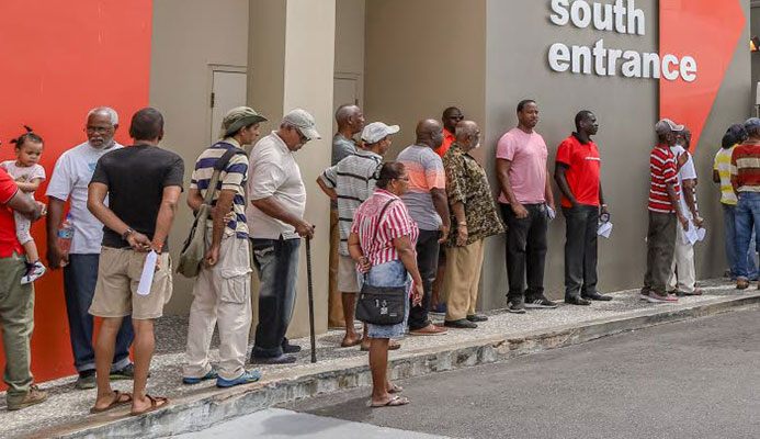 Members of the public wait in long lines to enter the Health Ministry's Men's Wellness Initiative Clinic at the Colposcopy Centre in the Mt Hope Women's Hospital yesterday.