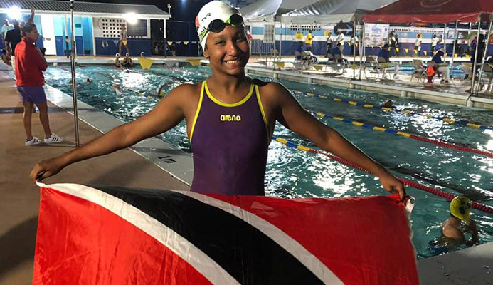 Jada Chatoor holding up the TT flag at the Carifta Championships in Barbados. PHOTO BY SHERDON PIERRE