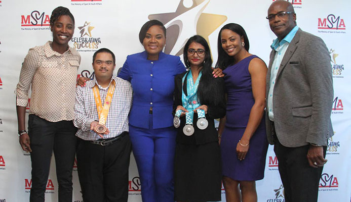Minister of Sport and Youth Affairs Shamfa Cudjoe, third from left, takes a photo with cricketer Britney Cooper, from left, bocce players Bernard Singh and Alicia Khan, cricketer Merissa Aguilleira and TT's first Olympic gold medallist Hasely Crawford at the Rewards, Recognition and Cheque Presentation Ceremony at the National Racquet Centre, Tacarigua, yesterday.