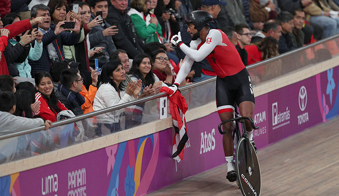 Njisane Phillip greets spectators after winning with teammates Keron Bramble and Paul Nicholas the gold medal in the cycling track men's team sprint final at the Pan American Games in Lima, Peru on Thursday. (AP)