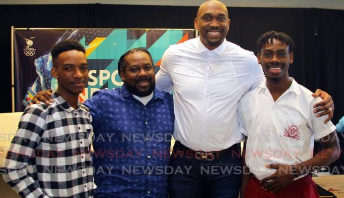 Kibwe Trim, former professional basketballer and founder of DreamChaser International Foundation, second from right, with brothers Zion Nicholas, left, and Israel Nicholas, right, recipients of the Scholar Athlete of the Year Award 2020 from the DreamChaser International Foundation, alongside their father Kieno Nicholas at the annual TT Olympic Committee Sport Industry Conference 2020, held at the Hyatt Regency, Port of Spain, on Thursday. - ROGER JACOB
