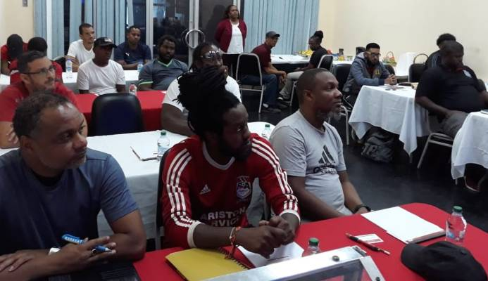 Susan Joseph-Warrick, TTFA Vice-President and WoLF President looks on while the participants listen attentively to Concacaf/Fifa instructor Anton Corneal at the start of the T&T Women's League Football (TTWoLF) hosted inaugural 'C' License Coaching Course at Ato Boldon Stadium, in Balmain, Couva on Monday.  TTWoLF