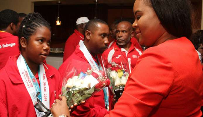 Sports Minister Shamfa Cudjoe (right) meets a member of the Special Olympics TT team during yesterday's reception at the VIP Lounge, Piarco International Airport.